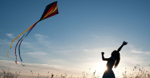 Young Girl having fun flying a multicoloured kite in the English countryside. Silhouette